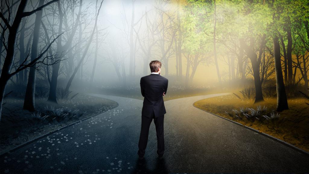 Geschäftsmann muss sich bei einer Weg-Gabelung entscheiden